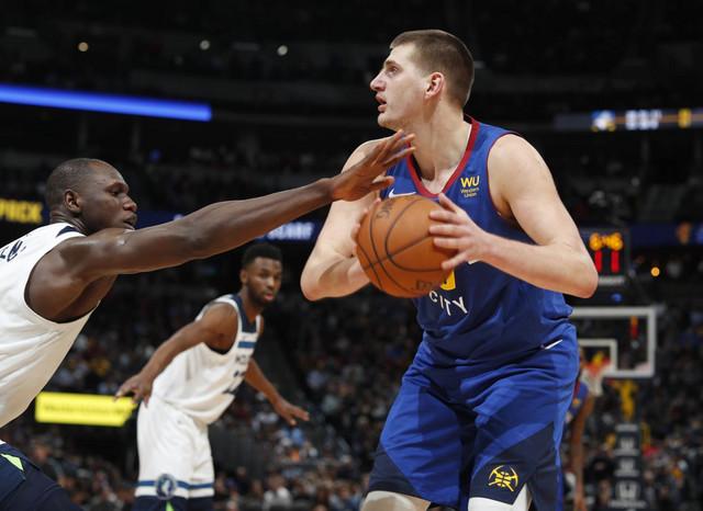 Nikola Jokić i Gorgui Dieng iz Minesote u deulu na meču NBA lige u Denveru