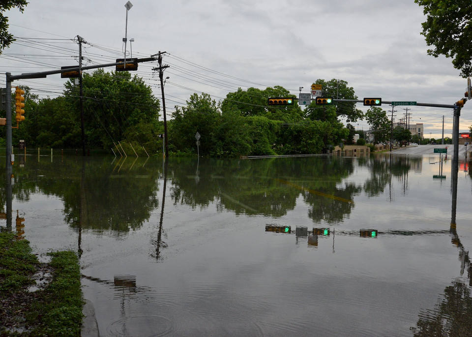 An intersection is flooded near the headwaters of the San Marcos River that flooded in San Marcos Texas