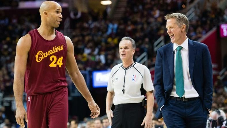 Richard Jefferson (L) of the Cleveland Cavaliers jokes with the Golden State Warriors' head coach Steve Kerr during the first half, at Quicken Loans Arena in Cleveland, Ohio, on December 25, 2016
