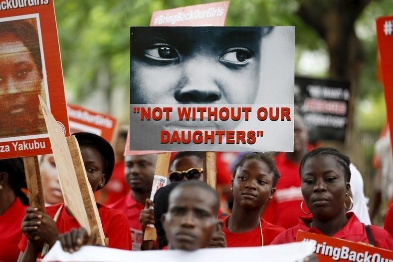 BBOG campaigners hold banners as they walk during a 2015 protest procession marking the 500th day since the Chibok girls' abduction. 112 of the girls remain in captivity after five years [Reuters/Akintunde Akinleye]