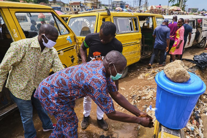Commuters wash hands preparatory to boarding the bus in Lagos (Pulse)
