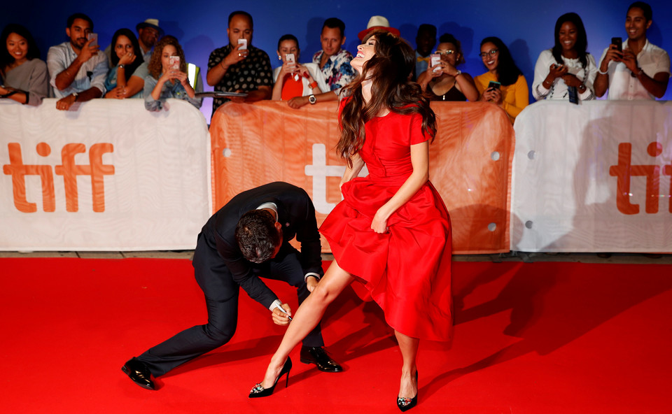 "Isaac pretends to autograph Le Bon's leg as they arrive on the red carpet for the film ""The Promise"" during the Toronto International Film Festival in Toronto"