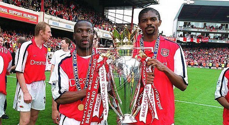 Lauren (left) and Kanu lift the English Premiership Trophy. Arsenal trained-coaching staff will be joined by Lauren as they help talent identification skills among Kenyan coaches as the country targets participation in the World Cup 2022 to be held in Qatar.