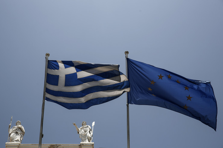 629153_a-greek-and-a-european-union-flags-flutter-in-front-of-statues-of-goddess-athenaap