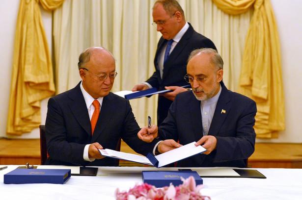 Szef MAEA Yukiya Amano oraz minister spraw zagranicznych Iranu Mohammad Javad Zarif podpisują porozumienie