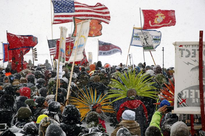 Veterans march with activists near Backwater Bridge just outside the Oceti Sakowin camp during a sno