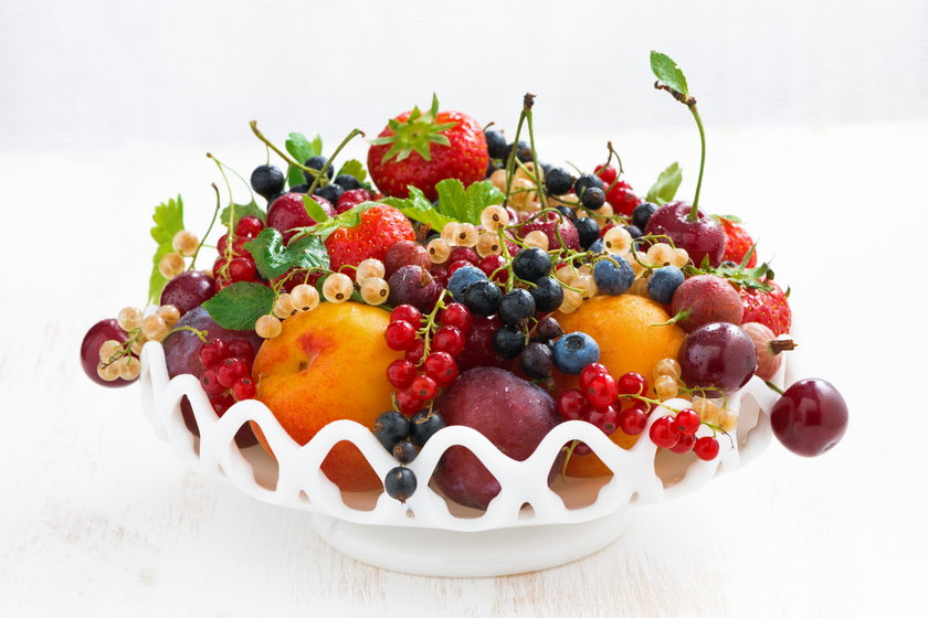 dish with seasonal fruit and berries on white table