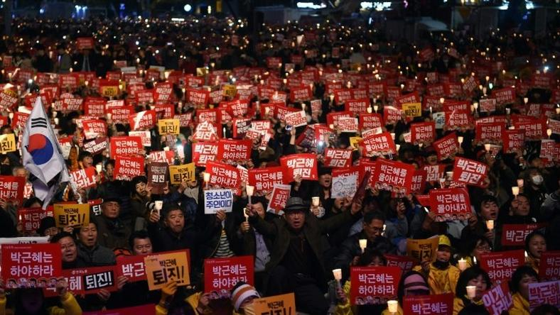 Protesters hold candles and banners calling for the resignation of South Korea's President Park Geun-Hye during an anti-government rally in central Seoul on November 19, 2016