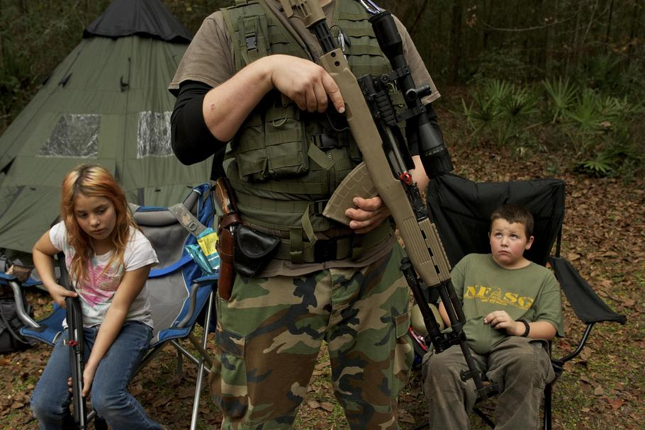 Member of the North Florida Survival Group wait with their rifles before heading out to perform enem