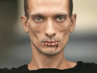 "Artist Pavlensky, a supporter of jailed members of female punk band ""Pussy Riot"" looks on with his mouth sewed up as he protests outside the Kazan Cathedral in St. Petersburg"