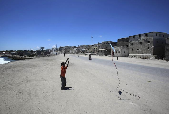 A boy plays with a kite in front of his home in the Hamaerweyne area of Mogadishu October 12, 2013.