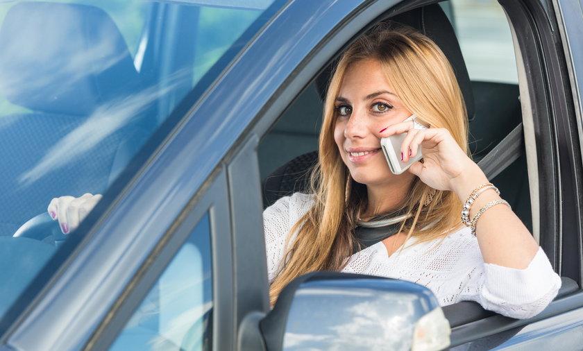 Kobieta rozmawiająca przez telefon w samochodzie