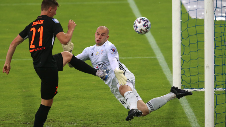 Zawodnik Zagłębia Lubin Bartosz Białek (L) strzela bramkę podczas meczu grupy spadkowej, 37. kolejki piłkarskiej Ekstraklasy Górnikiem Zabrze