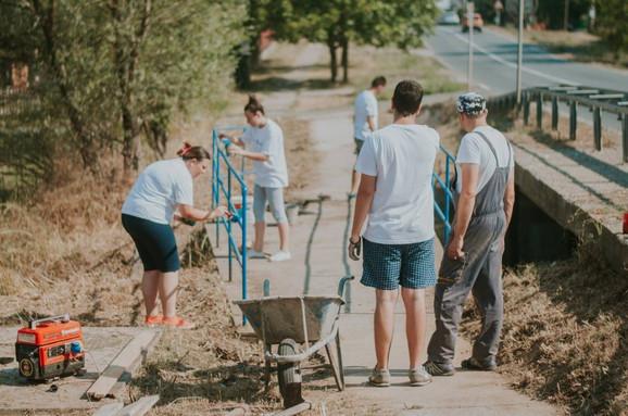 Vrućina ih nije sprečila da doteraju most na ulazu u selo