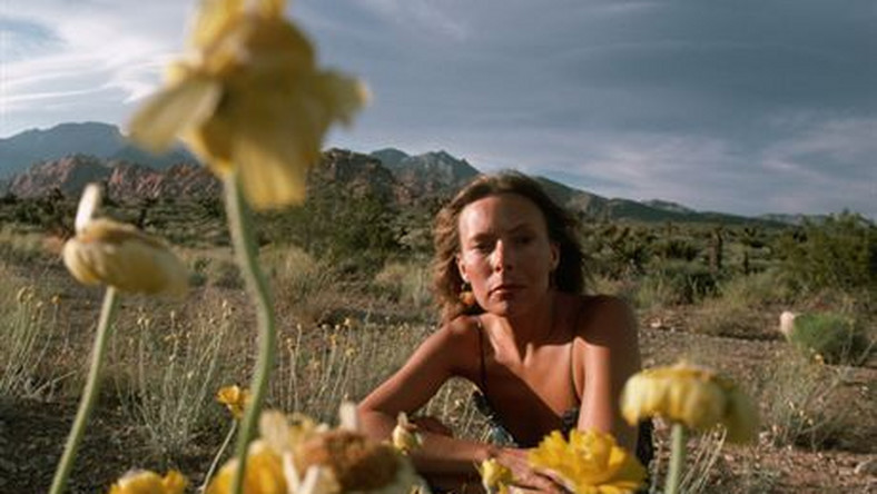 May 1978, Nevada, USA --- Singer-songwriter Joni Mitchell rests in the Nevada desert among yellow flowers. Mitchell remains one of the most acclaimed songwriters and performers of rock music since the sixties.FOT. CORBIS