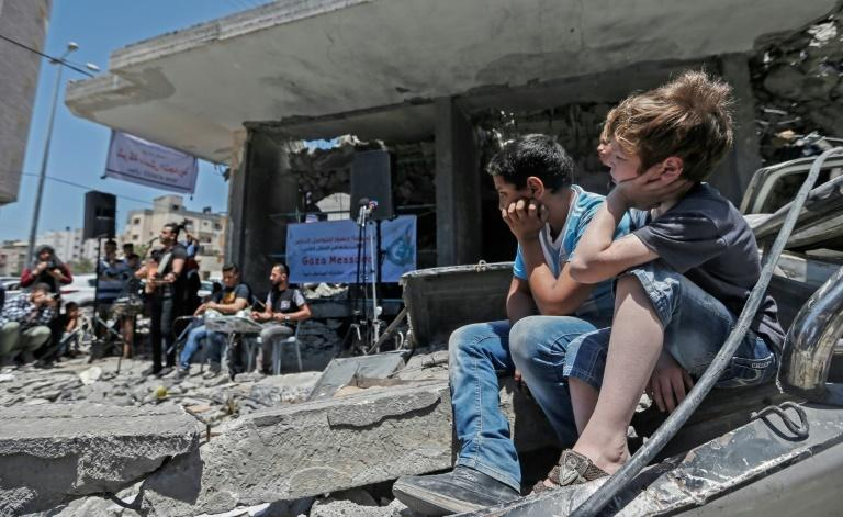 Palestinian children watch musicians perform in the shadow of a building destroyed by an Israeli air strike this month in response to Palestinian rocket fire