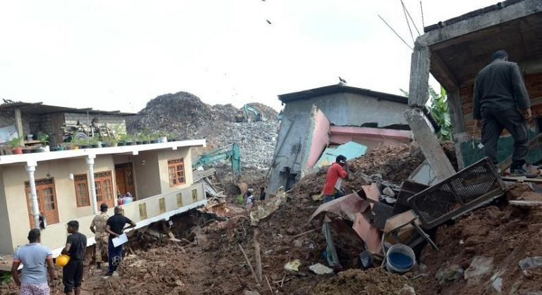 Residents and rescuers check damaged homes at the site of a collapsed garbage dump near Colombo, on April 15, 2017