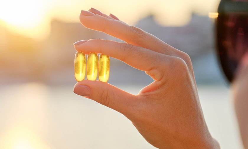 Yellow gel capsule vitamin d omega-3 in womans hand, sun sea background