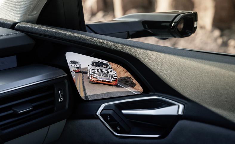 W Audi e-tron debiutują – w skali światowej jeśli chodzi o samochody produkowane seryjnie – opcjonalne, wirtualne lusterka zewnętrzne. To małe kamerki na płaskich wspornikach. Rejestrowany przez nie obraz wyświetlany jest na ekranach OLED umiejscowionych w przejściu między deską rozdzielczą, a drzwiami