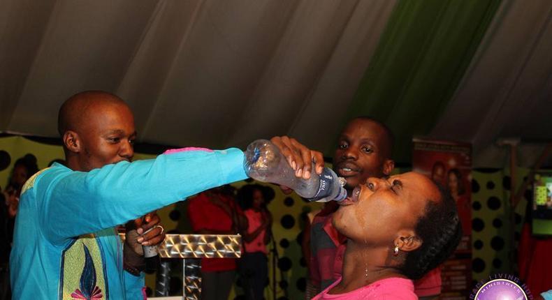 Prophet Light Monyeki of Grace Living Hope Ministries gives a congregant some poison