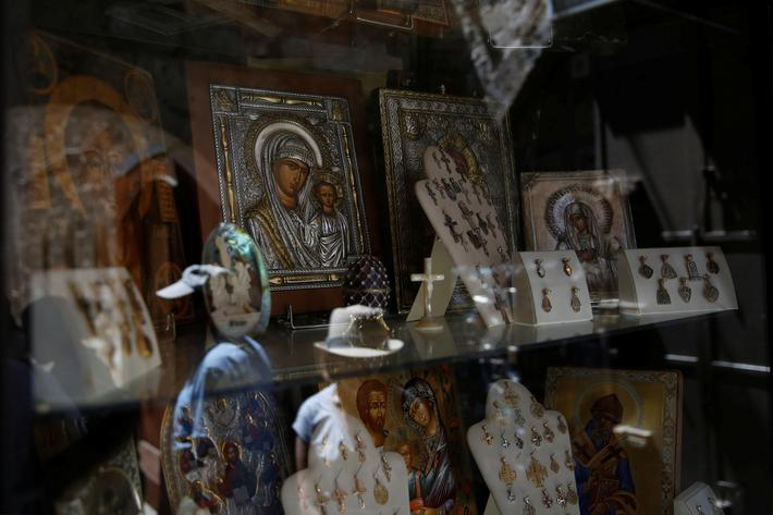 Tourists are reflected in the window of a shop selling Christian souvenirs in the Christian Quarter