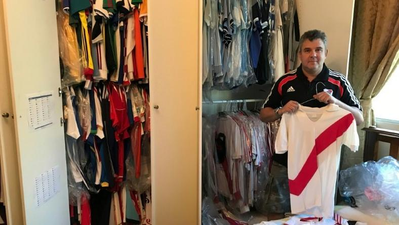 River Plate fanatic Javier Maluf poses with the Argentine's club jersey's at his home in Doha before setting out on his long trek to Madrid