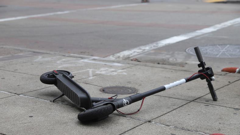 Porzucona hulajnoga elektryczna na chodniku