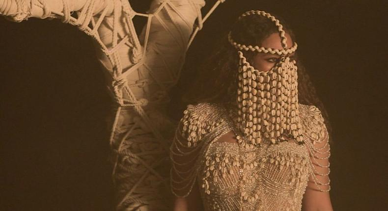 Beyonce has been heavily influenced by African culture especially Yoruba culture as of late. Here she is wearing a face mask made from cowries (Pink Now)