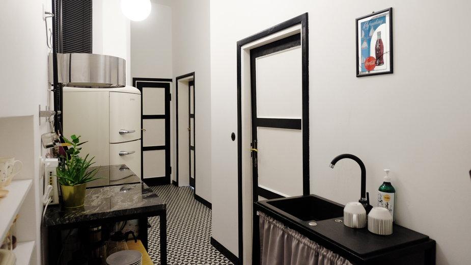 Małgosia Caban zaprojektowała małe mieszkanie, w którym czarne akcenty kontrastują z bielą