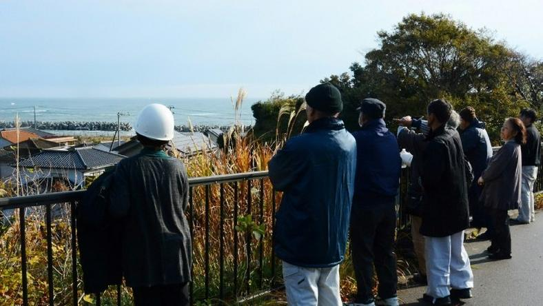 Local residents look out to sea from higher ground after evacuating their homes following a 6.9 magnitude earthquake and tsunami alert in Iwaki, Fukushima prefecture, on November 22, 2016