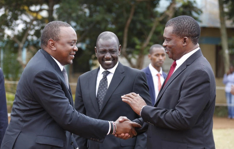 President Uhuru Kenyatta consoles National assembly speaker Justin Muturi during the burial service of the mother of National Assembly Speaker Justin Muturi in Embu County, looking on is DP WIlliam Ruto.