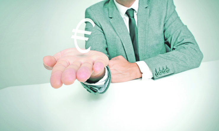 stock-photo-a-businessman-sitting-in-a-desk-showing-a-euro-sign-in-his-hand-175249313