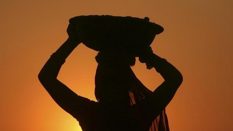 A woman labourer carrying cement is silhouetted against the setting sun at the site of a commercial complex on the outskirts of Jammu November 22, 2012.