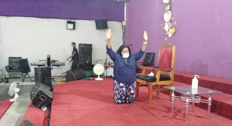 Bishop Margaret Wanjiru kneels in prayer at her church minutes after being discharged from hospital where she underwent treatment for Coronavirus