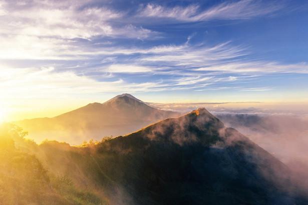 Wulkan Batur Wulkan Batur, choć wciąż aktywny, dostępny jest dla wszystkich. Wznosi się zaledwie na wysokość 1,700 metrów ponad poziom morza, ale widok z jego szczytu jest naprawdę spektakularny – zwłaszcza podczas wschodu słońca, kiedy to wspaniały krajobraz powoli wyłania się z ciemności. Jeżeli chcemy tego doświadczyć, trzeba wyruszyć około trzeciej nad ranem. Trasa z wioski Toya Bungkah, leżącej na skraju jeziora u stóp wulkanu, zajmuje około dwóch godzin. Pokonanie jej nie jest męczące, jedyne o czym trzeba pamiętać to zakryte obuwie, ponieważ na ścieżce zdarzają się kamienie. Na wierzchołek należy dotrzeć około piątej, ale już wcześniej czeka Was wiele niezapomnianych przeżyć. Jeszcze zanim słońce zacznie wyłaniać się zza horyzontu, cała okolica budzi się wyczuwając nadchodzący dzień. Narastające odgłosy podekscytowanych zwierząt, dźwięki odbijające się od krateru wulkanu, to przeżycie tak emocjonujące, że zanim się obejrzycie będziecie już na szczycie wulkanu. Wystarczy jeszcze tylko chwilę poczekać na świt. Pierwsza łuna słonecznego światła wynurza się zza góry Agung. Promienie stopniowo odsłaniają kolejne szczyty leżące po przeciwległej stronie jeziora Danau Batur. Widzimy jak światło odbija się od jego tafli, w końcu pada także na obręcz krateru na którym stoimy, odsłaniając olbrzymie wulkaniczne stoki pokryte popiołem. Gdzieniegdzie widać nawet parę unoszącą się nad aktywnymi pęknięciami. Ten widok uświadamia nam, że rzeczywiście stoimy na wulkanie, na najaktywniejszym sejsmicznie obszarze na całym Bali! To najlepszy świetlny show, jaki kiedykolwiek przyszło nam oglądać. Z pewnością trudno o lepszą śniadaniową scenerię, dlatego bardzo często zwieńczeniem wyprawy jest wspólne śniadanie – jajka na twardo gotowane bezpośrednio nad parą wydobywającą się ze skalnych szczelin.