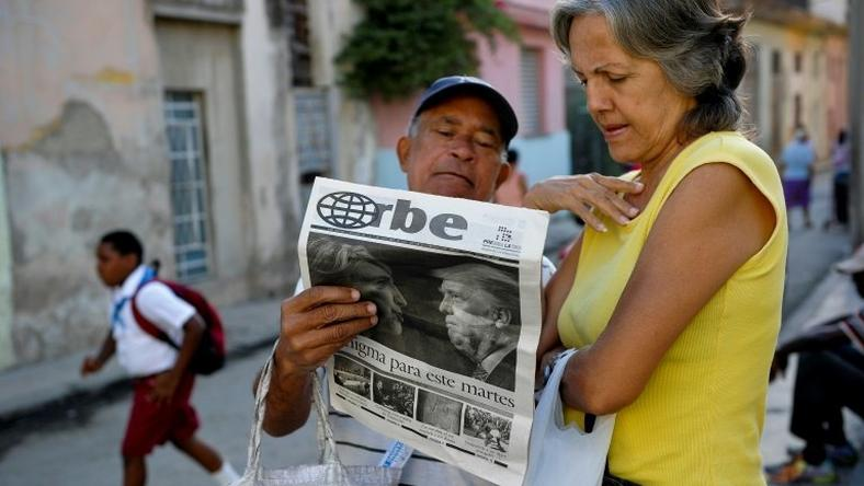 Cubans read a newspaper with its front page informing of the victory of US presidential candidate Donal Trump in a street of Havana, on November 9, 2016