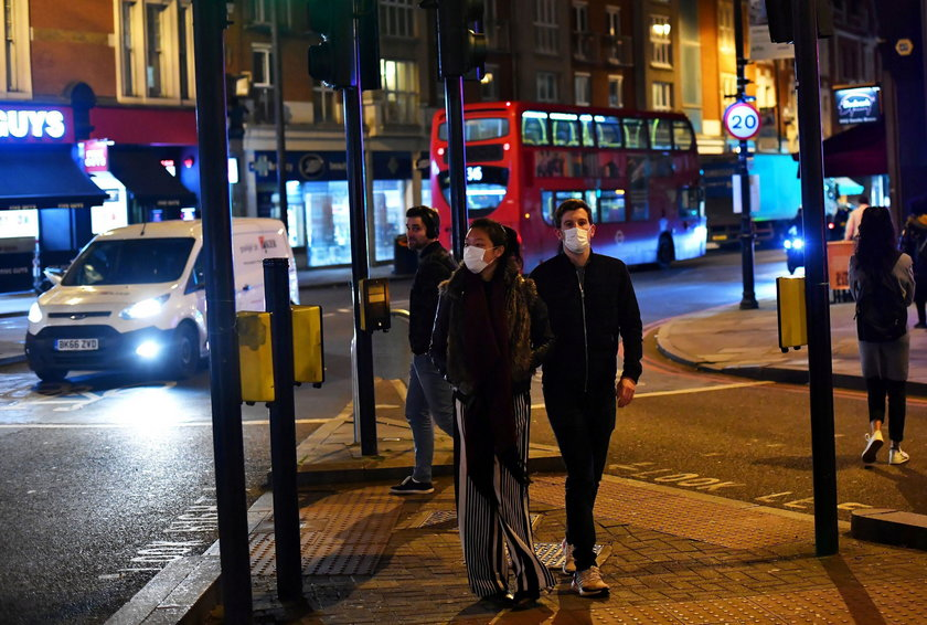 A couple wearing face masks walk down Clapham High Street in London