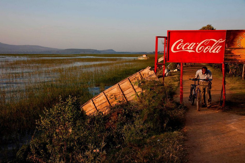 A man pushes his bike through a Coca-Cola sign in Awasa Lake, Ethiopia. (Mashable)