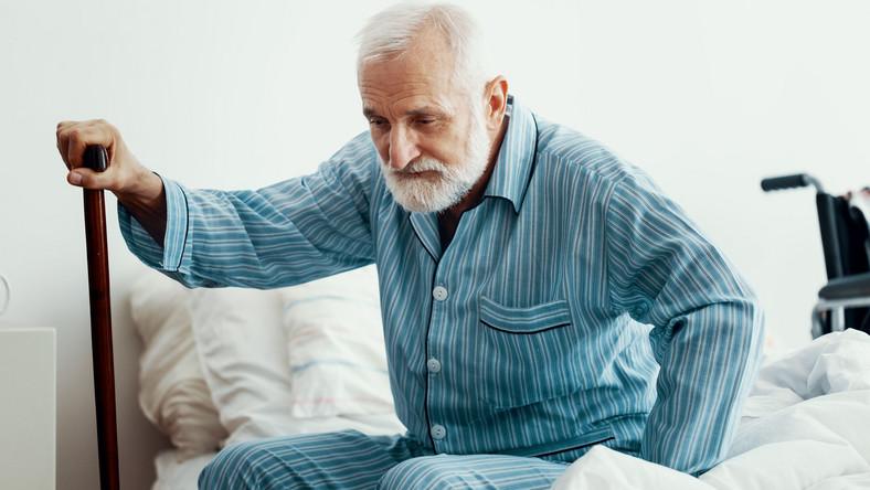 Starszy mężczyzna siedzi na łóżku, w pidżamie