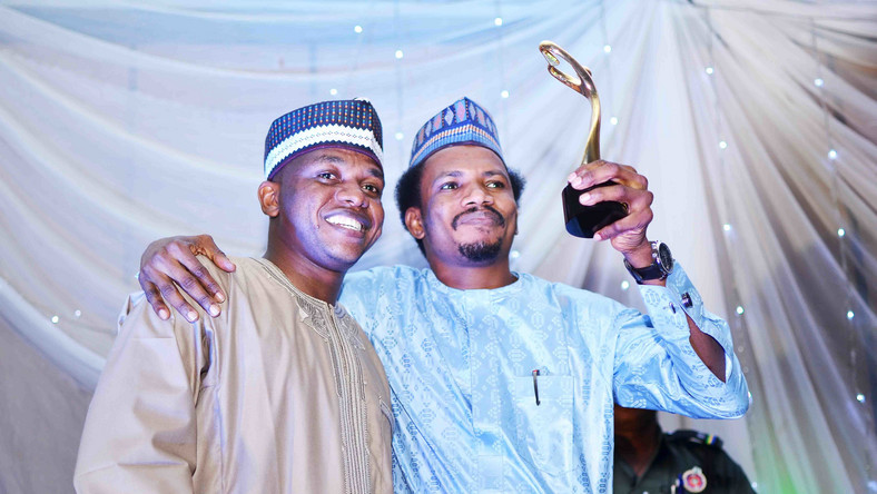 """Senator Elisha Abbo (right) raises his """"Beacon of Hope"""" award. """"Beacon of Hope"""" was his campaign slogan before he was elected as the youngest senator in the 9th Senate. Weeks before his inauguration, he beat up and arrested a woman for telling him to calm down during a heated exchange inside a sex toy shop in Abuja [The Gazette Nigeria]"""