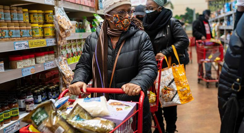 A woman wearing a mask moves her shopping cart December 3, 2020 in a Trader Joe's supermarket in New York City.