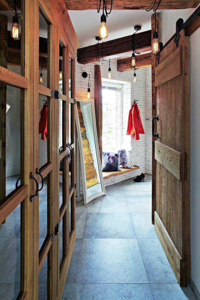"""BELKI POD SUFITEM, drewniane drzwi z metalowymi okuciami, ławeczka pod oknem zrobiona z desek – """"góralska chałupa"""" zaprasza już od wejścia."""