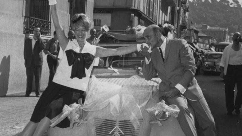 Actress Janis Paige being kissed on the hand by her new husband, lyricist Ray Gilbert, as the two sit on the bonnet of their 'Just Married' car, outside the church on their wedding day in France, 1962.