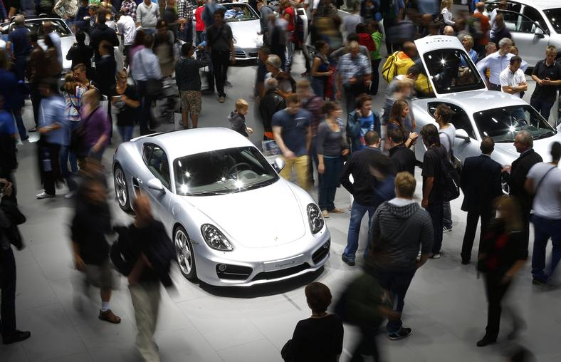 Visitors stroll over the stand of German car manufacturer Porsche to watch a Porsche cayenne S (L) at the Frankfurt Motor Show.