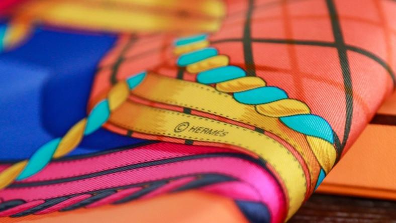 Apaszka z domu mody Hermès to z pewnością klasyk, który nigdy nie wyjdzie z mody, dlatego warto mieć go w swojej szafie. Do produkcji jednej apaszki zużywa się…450 kilometrów jedwabnej nici, a na przestrzeni wielu dekad swoimi pędzlami ozdabiało je aż 100 różnych artystów! Od początku swego istnienia apaszka doczekała się ponad 1500 wersji. - Bardzo często, aby zweryfikować pochodzenie produktu, musimy posługiwać się różnymi przyrządami, w tym również wagami. Dlaczego? Oryginalna apaszka Hermès o wymiarach 90 x 90 cm powinna ważyć 63 gramy, natomiast sztuczne tkaniny, z jakich wykonuje się podróbki zwykle będą cięższe – mówi Dorota Partycka-Busoni. - Kolejną rzeczą są kolory: w podróbkach, na odwrocie chusty, wzór nie jest regularnie odbity lub też saturacja nie jest odpowiednia. No i w końcu brzeg, który zawsze powinien być ręcznie podszyty, NIGDY maszynowo!