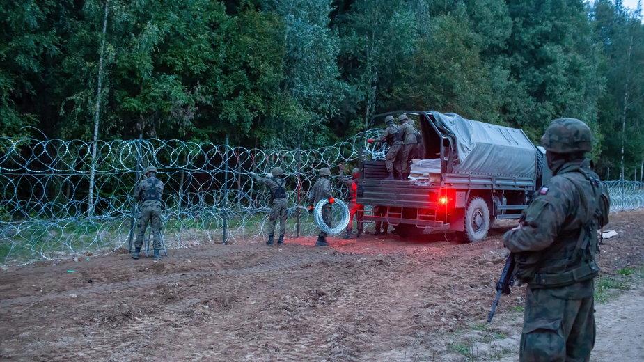 Żołnierze budujący płot na granicy polsko-białoruskiej