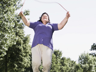 overweight woman skipping in park