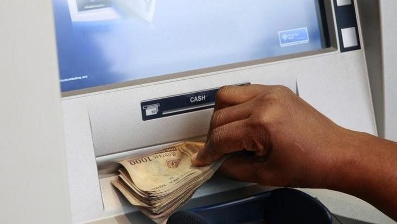 A woman takes Nigerian Naira from a bank's automated teller machine in a file photo. REUTERS/Akintunde Akinleye