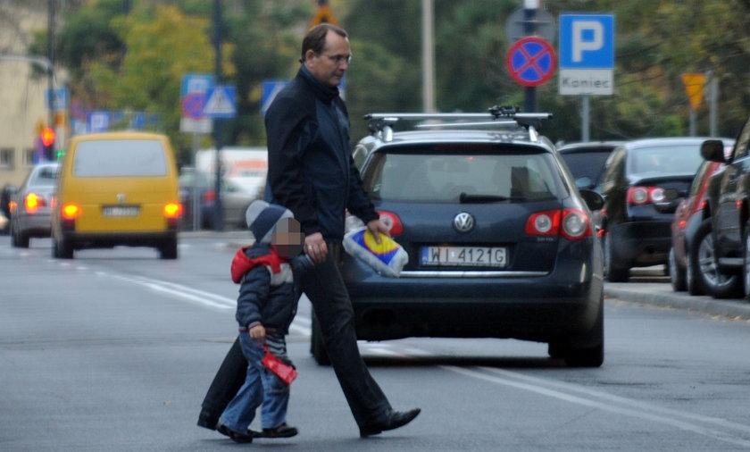 Eugeniusz Kłopotek przeprowadza syna przez ulicę.