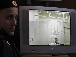 A bailiff stands next to a screen with a live broadcast of a court hearing an appeal by an oppositio